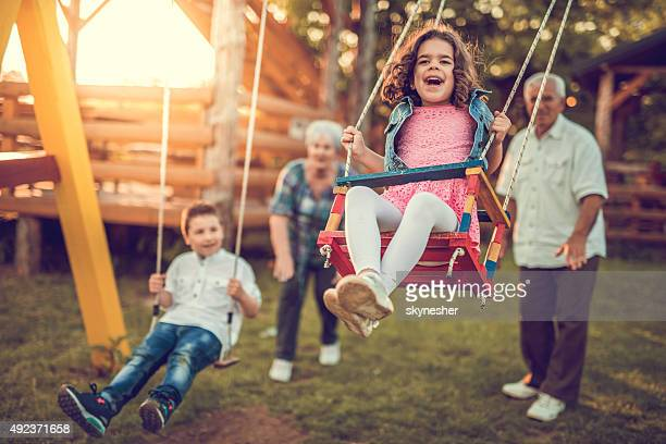 Grandparents swinging their grandchildren.