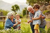 Grandparents talking to children in yard
