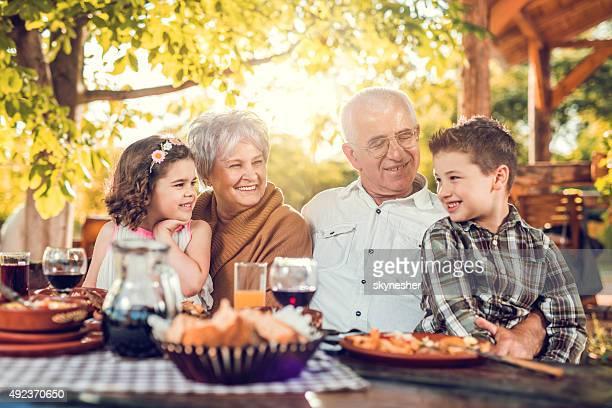 Abuelos hablar con nuestros nietos durante el almuerzo en el restaurante.