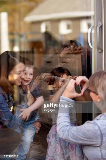 grandparents visiting grandkids during quarantine through window - photographed through window stock pictures, royalty-free photos & images