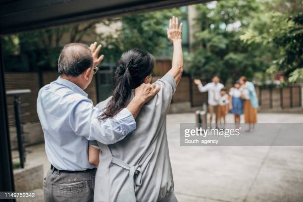 grandparents waiting for their family who came to visit - waving stock pictures, royalty-free photos & images
