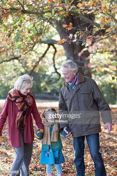 Abuelos caminando en el parque con granddaughter