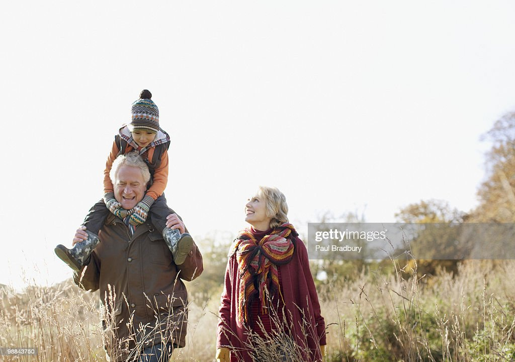 Grandparents walking outdoors with grandson : Stock Photo
