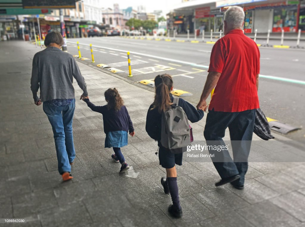 Grandparents Walking their Two Granddaughters ro School : Stock Photo