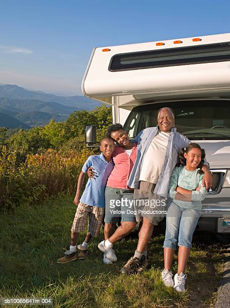 Grandparents with grand children (10-13) leaning against motorhome, smiling