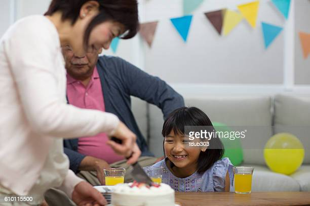 Grandparents with grandchildren eating cake at a birthday party