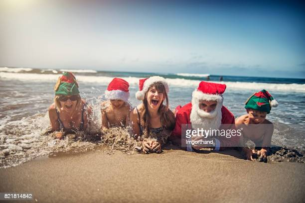 Grandparents with grandchildren having christmas on beach