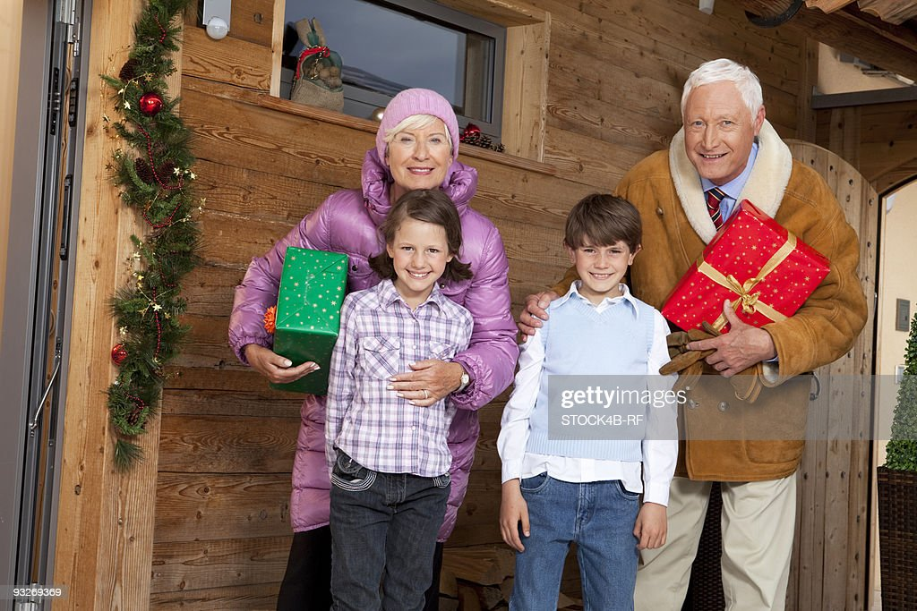 Grandparents With Grandchildren Holding Christmas Presents At Wooden ...