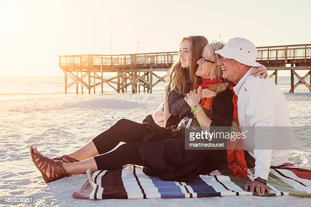 Grandparents with granddaughter enjoying sunset on the beach.