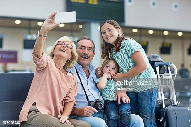 Grandparents with granddaughters taking a selfie in the airport