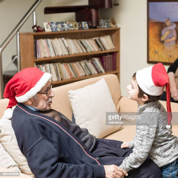 Grandson An Great Grandfather Wearing Santa Hat And Chatting At Home