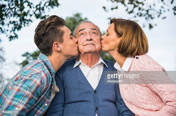 Grandson and daughter kissing senior mans cheek