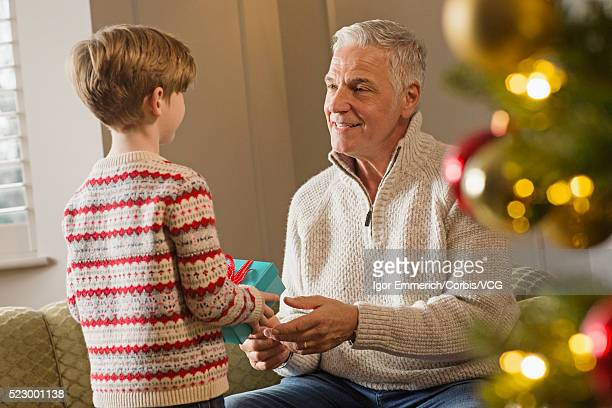 Grandson and grandfather exchanging Christmas gifts