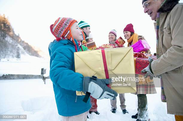 Grandson (8-10) and grandfather holding gifts in snowscape with family