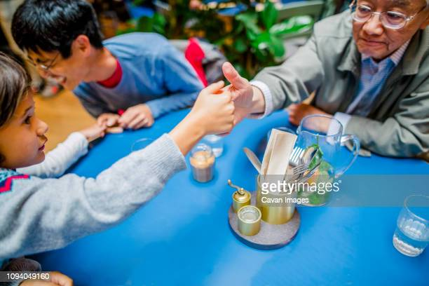 grandson and grandfather playing thumb wrestling at restaurant - mixed wrestling stockfoto's en -beelden