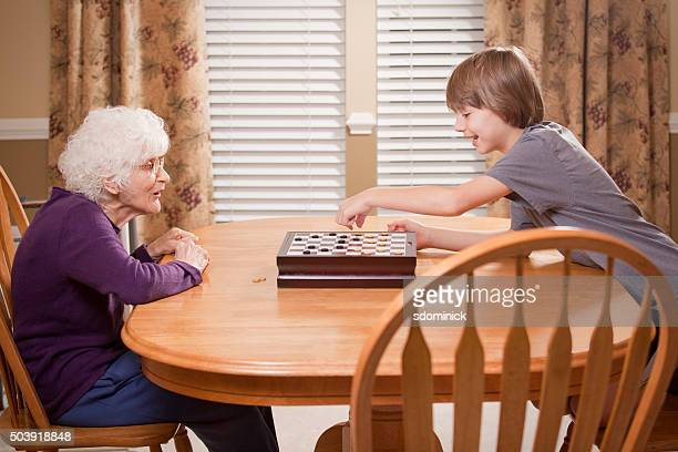 grandson and grandmother checker game - chequers stock photos and pictures