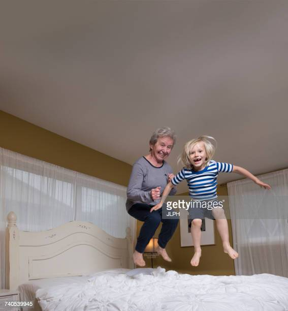 Grandson and grandmother jumping on bed