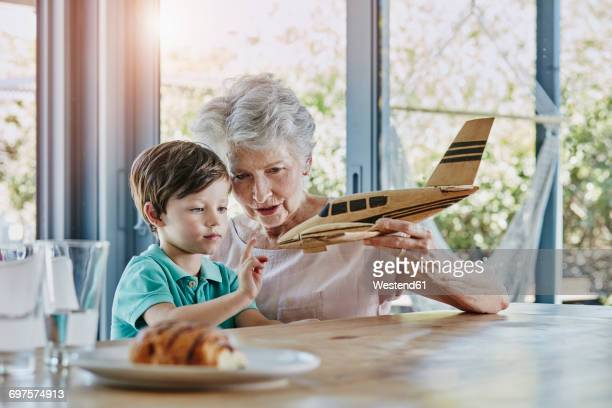 Grandson and grandmother playing with toy airplane