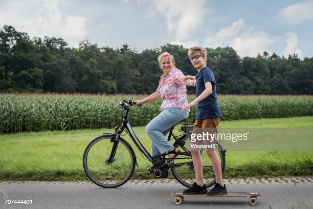 Grandson and grandmother riding bicycle and skateboard together