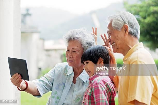 Grandson and grandparents taking selfie with digital tablet