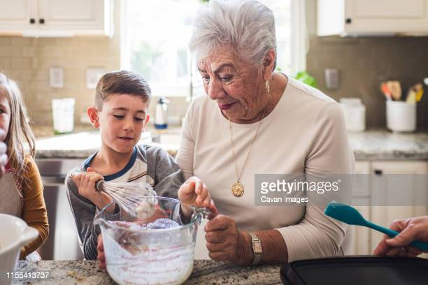 grandson and great grandma making breakfast pancakes in the kitchen - family reunion stock pictures, royalty-free photos & images