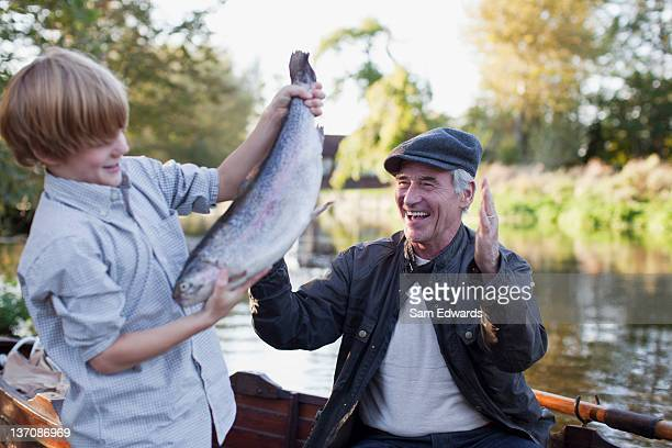 grandson catching fish with grandfather cheering in background - fish love stock photos and pictures