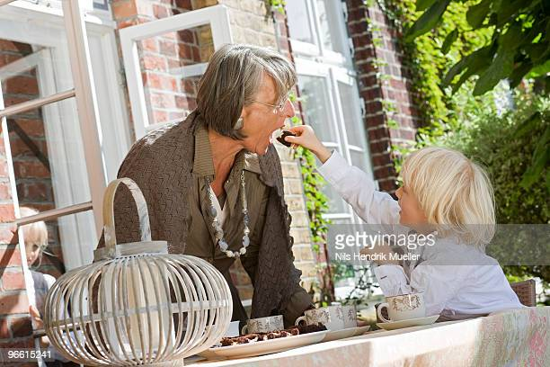grandson feeding grandma with cake