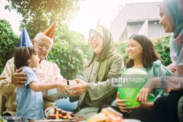 grandson giving a birthday present to his grandmother - 僧衣 ストックフォトと画像