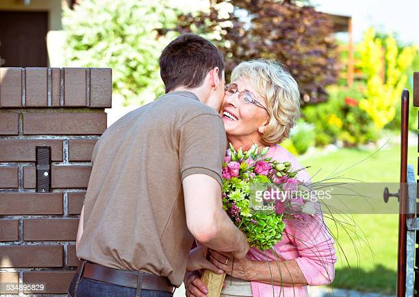 Grandson giving flowers to his grandmother