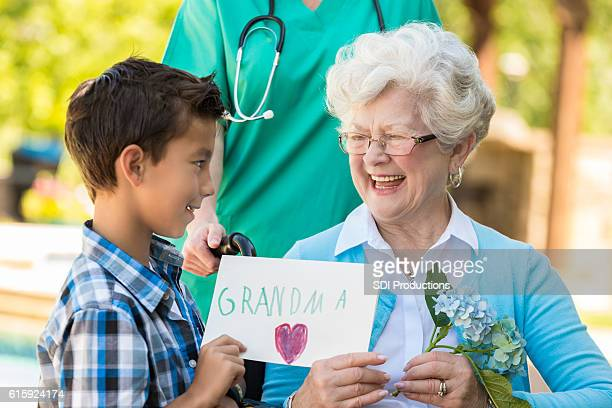 Grandson giving his grandmother a get well card and flowers