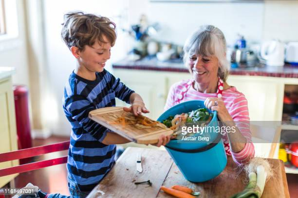 grandson helping with kitchen waste for composting - chores stock pictures, royalty-free photos & images