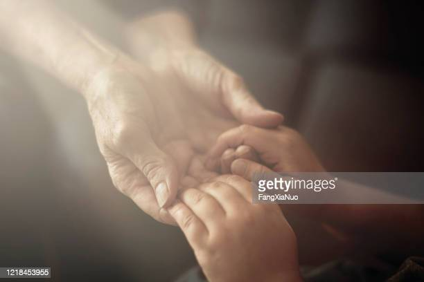 grandson holding grandmother hands close up view - religious blessing stock pictures, royalty-free photos & images