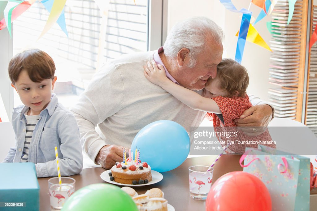 Grandson hugging Grandfather at birthday party : Stock Photo