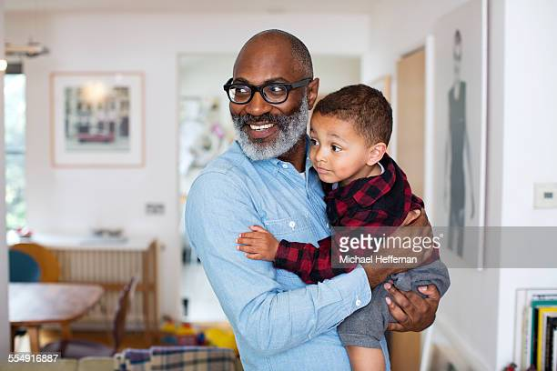 grandson in grandfathers arms - active seniors stock pictures, royalty-free photos & images