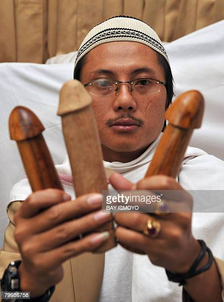 Grandson of Mak Erot Indonesia's legendary supernatural lengthener of members Saipuloh shows his equipments three large wooden penises at his clinic...