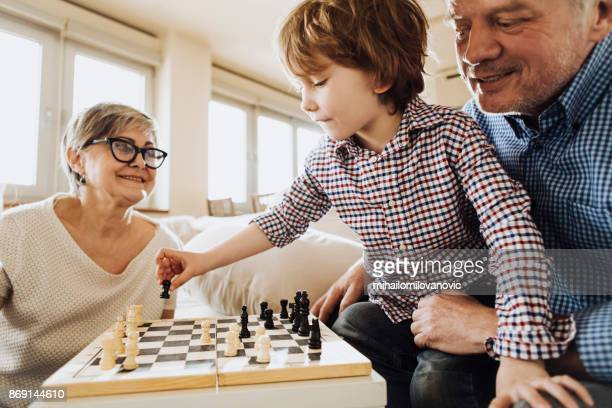 Grandson playing chess against grandma