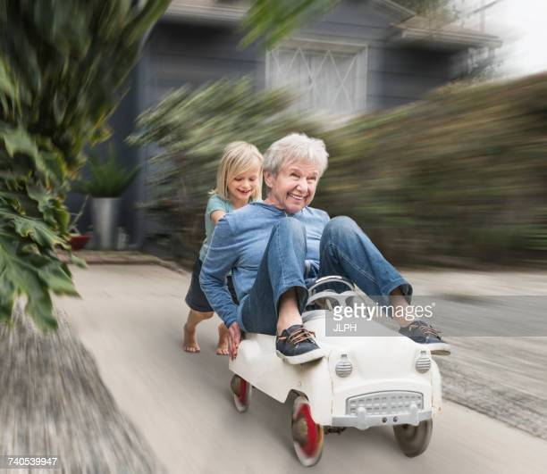 grandson pushing grandmother on his toy car - young at heart stock pictures, royalty-free photos & images