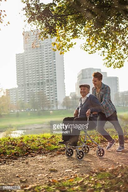 Grandson pushing happy senior man with wheeled walker