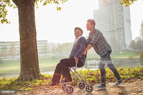 Grandson pushing happy senior man with wheeled walker