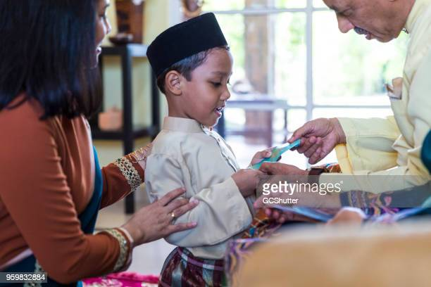 grandson receiving gift from grandfather during eid - eid mubarak stock pictures, royalty-free photos & images