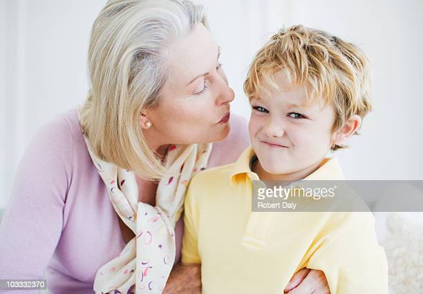 grandson refusing grandmothers kiss - weigeren stockfoto's en -beelden