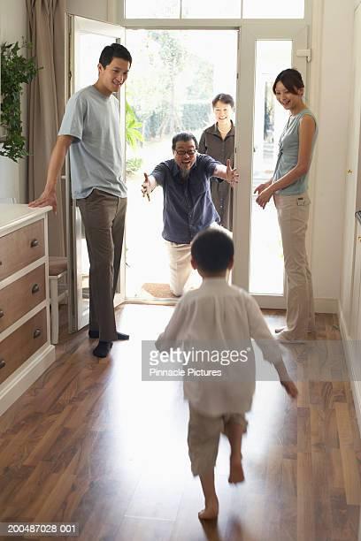 Grandson (4-5) running to greet grandfather at doorway