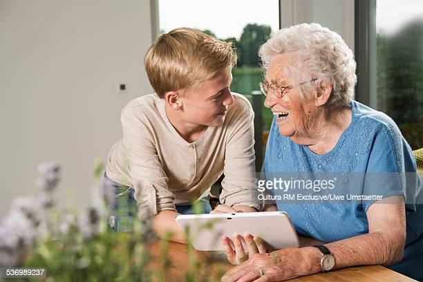 Grandson showing digital tablet to grandmother