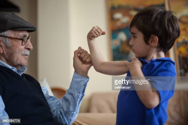Grandson Showing His Biceps To Great Grandfather