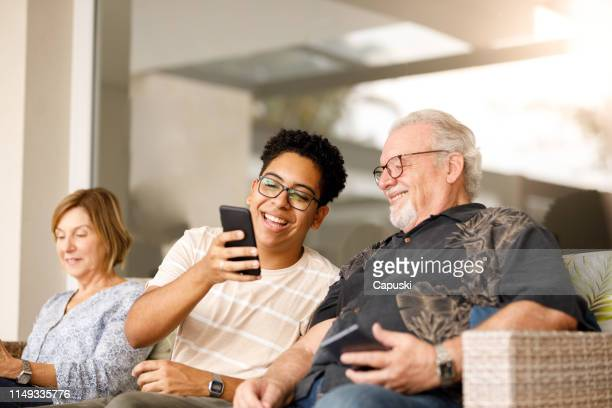 grandson showing something on cellphone to grandfather - meme stock pictures, royalty-free photos & images