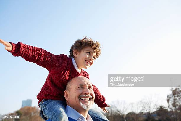 Grandson sitting on grandfathers shoulders, arms out smiling