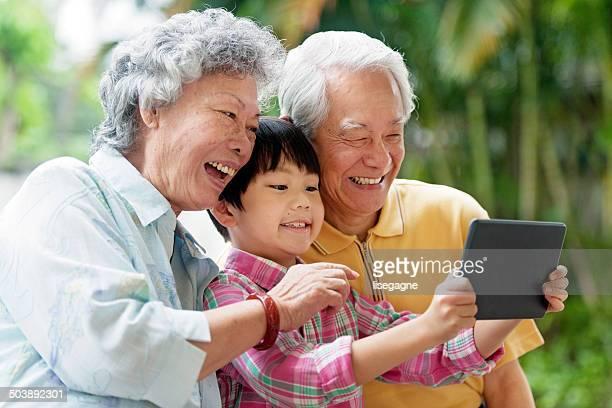 grandson teaching grandparents how to use a digital tablet - aziatische etniciteit stockfoto's en -beelden