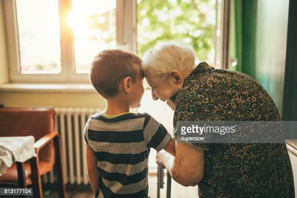 grandson visiting his granny in nursery - affectionate stock pictures, royalty-free photos & images