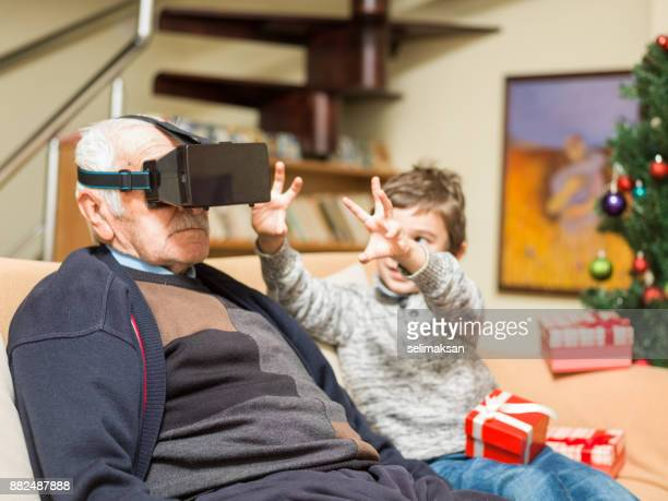 Grandson Watching Grandfather Experiencing VR Technology