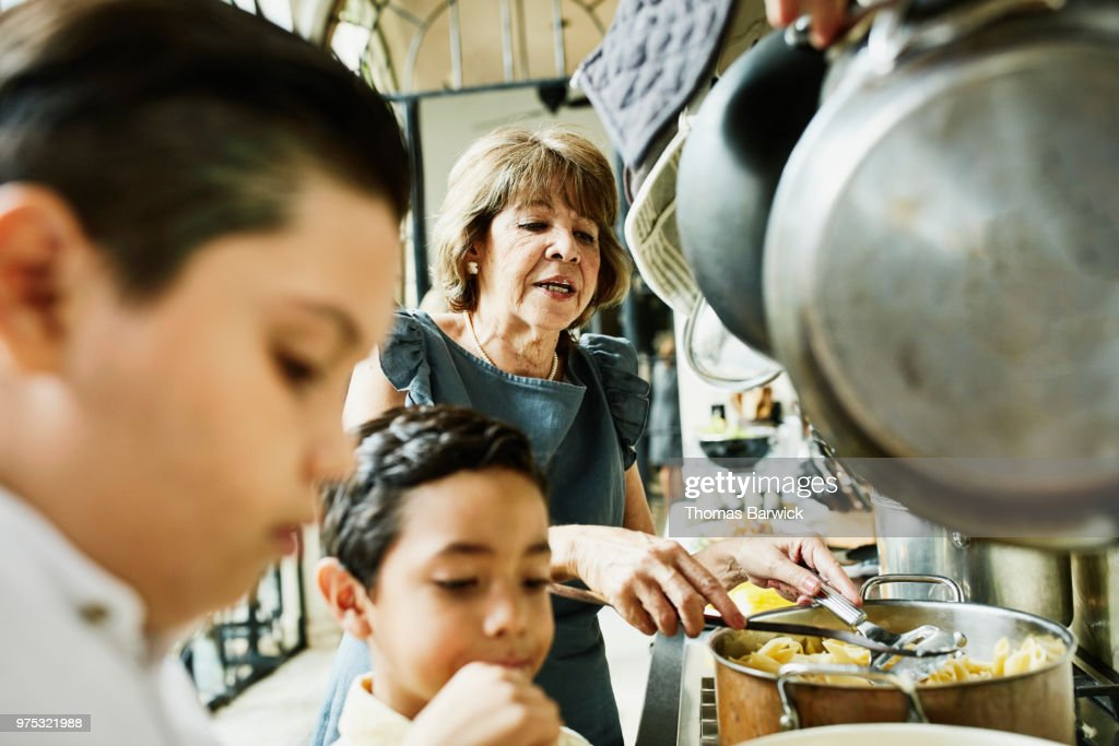 Grandsons helping grandmother prepare food in kitchen for family dinner : Stock Photo